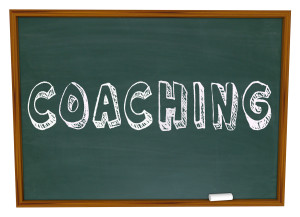 The word Coaching on a blackboard or chalkboard to symbolize lea