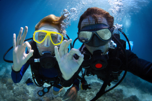 Underwater shoot of a young couple diving with scuba in a tropic